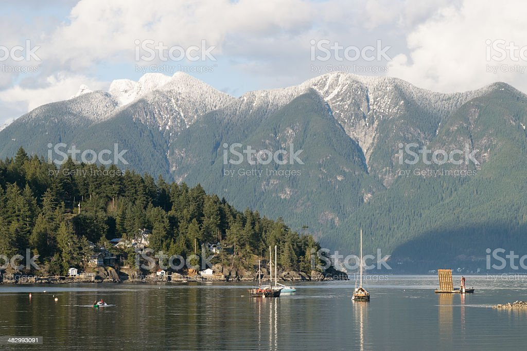 Mountains, ocean, boats and land in late afternoon stock photo