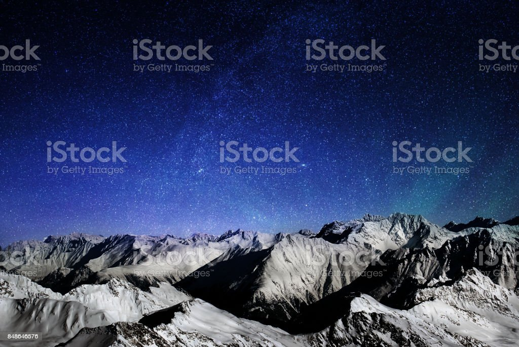 Mountains of the Alps at night, snowy peaks of a mountain range under a large starry sky stock photo