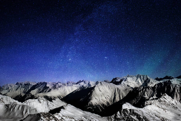 mountains of the alps at night, snowy peaks of a mountain range under a large starry sky - snowy mountains stock photos and pictures