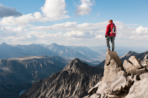 A man on top of a mountain looking at view