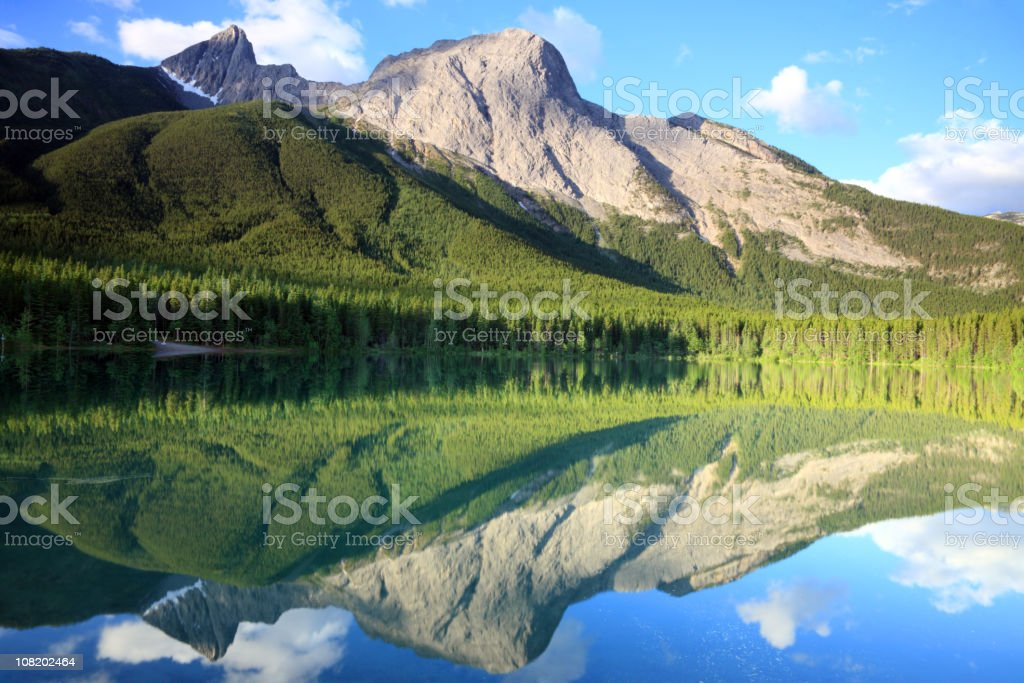 A mountains reflection on the water below royalty-free stock photo