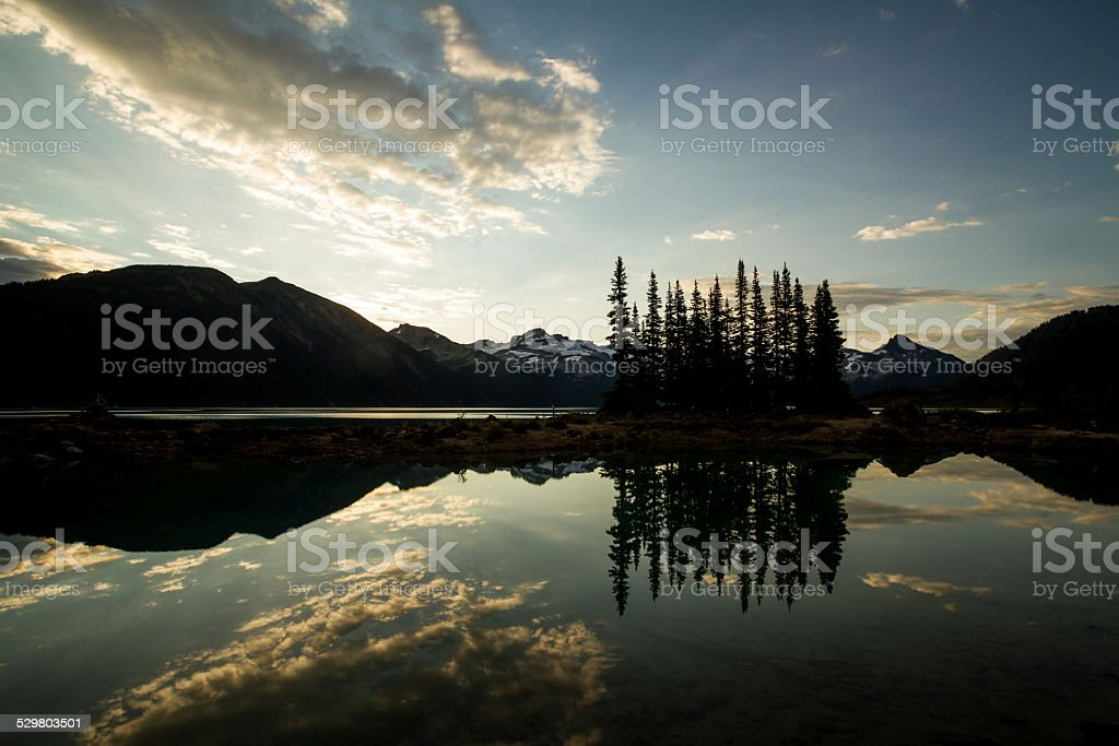 Mountains Silhouetted Over a Lake at Sunrise stock photo