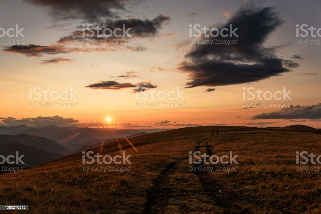 Beautiful sunset with sun rays over the contours of the mountains and...