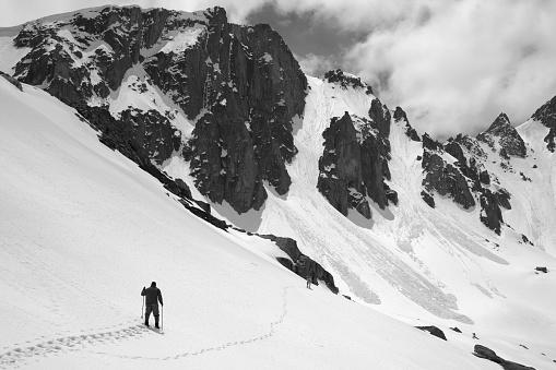 Snowy mountains with avalanche traces, sunlit cloudy sky, hiker with ski poles and dog on snowy slope at sunny day. Turkey, Kachkar Mountains, Pontic Mountains. Black and white toned landscape.