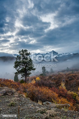 San Juan Mountains Covered with Snow in Autumn Covered with Storm Clouds and Fog with Brightly Colored Trees Below