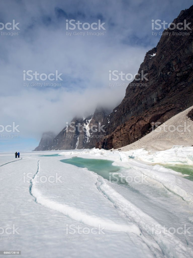 Mountains with dramatic Arctic sky and sea ice with meltwater stock photo