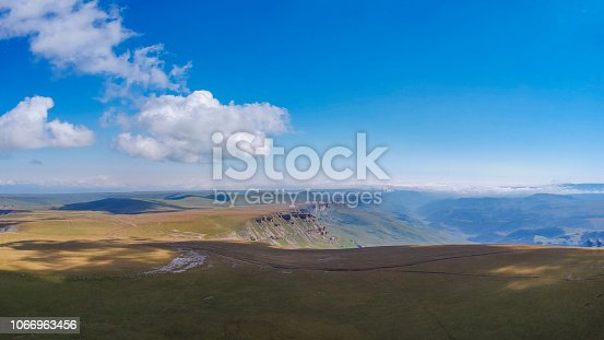 Mountains with high altitude quadrocopter in summer, clouds and fields around