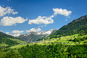 The idyllic mountain-village Marul in Vorarlberg in the Austrian alps. There is forest all around and a mountain-range with some white clouds and blue sky in the background.