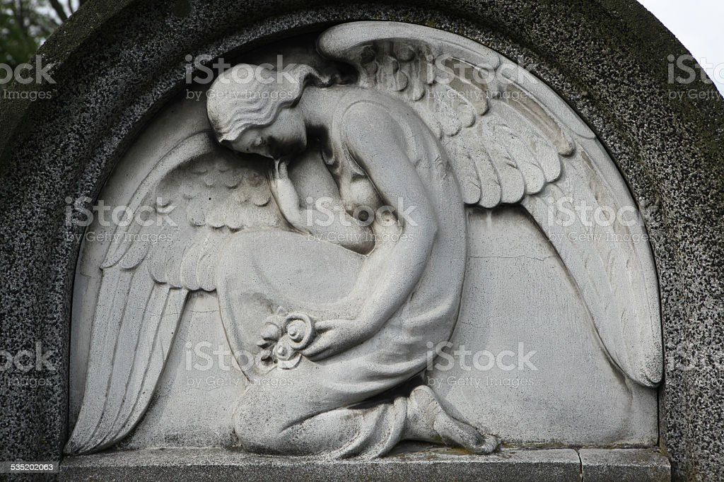 Mourning angel at the abandoned cemetery. stock photo