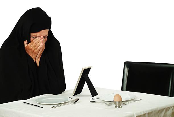 mourning moslima oder nonne mit ei am frühstückstisch - trauer abschied tod stock-fotos und bilder