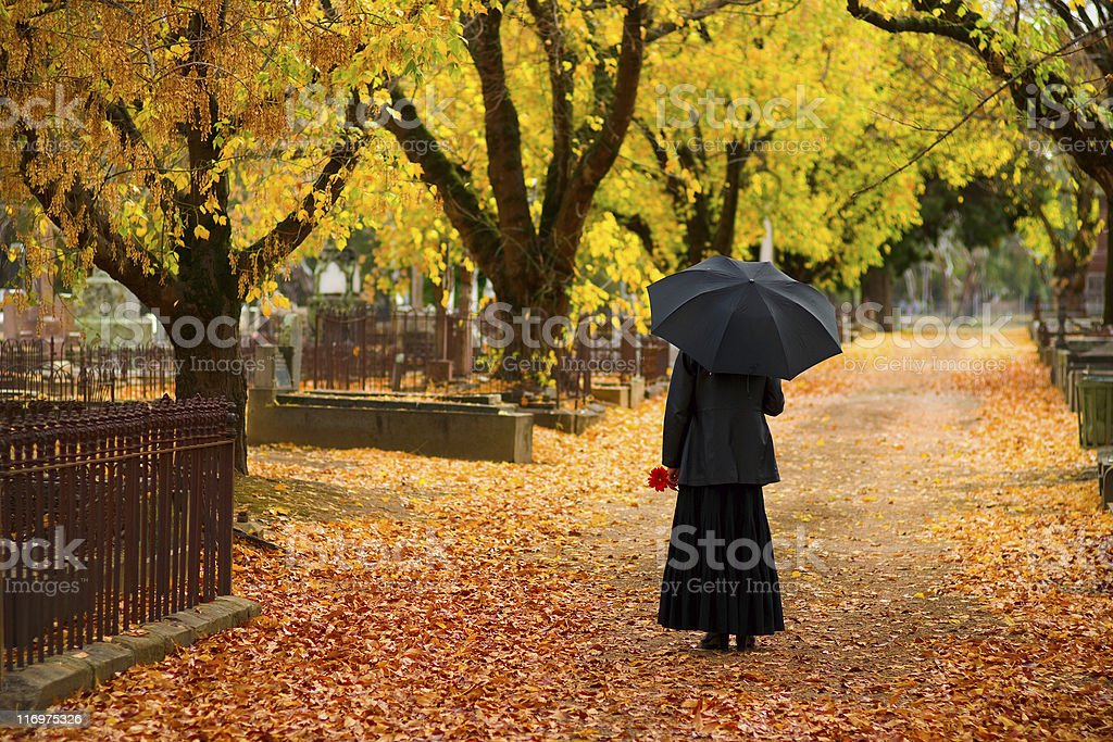 Mourning Woman wearing black in cemetery in fall stock photo