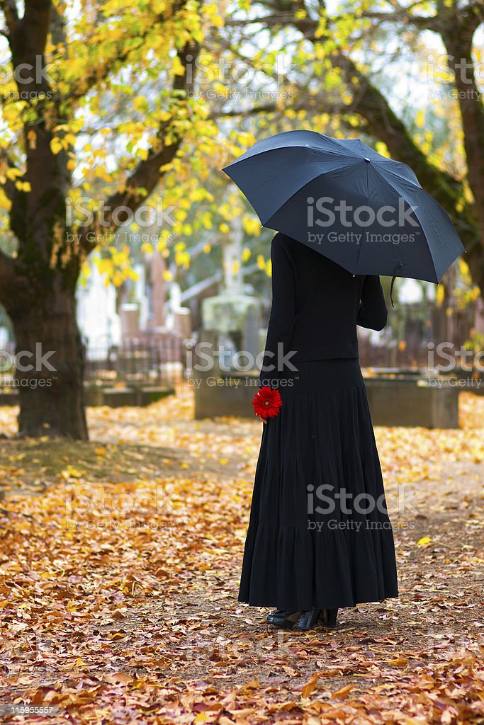 Mourning woman with black umbrella in cemetery in fall royalty-free stock photo