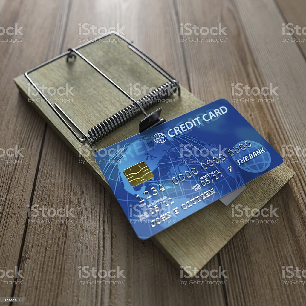 A mouse trap with a credit card on a wooden floor stock photo