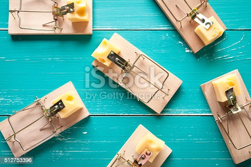 Mouse traps with cheese on turquoise table. This file is cleaned and retouched.