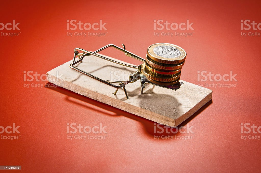 Mousetrap with Euro coins, isolated on red background royalty-free stock photo