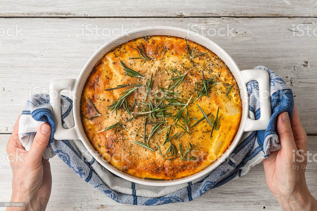 Moussaka with rosemary in ceramic pan in hand top view stock photo