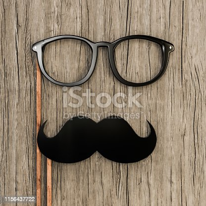 istock moustache and eyeglasses on wooden top 1156437722