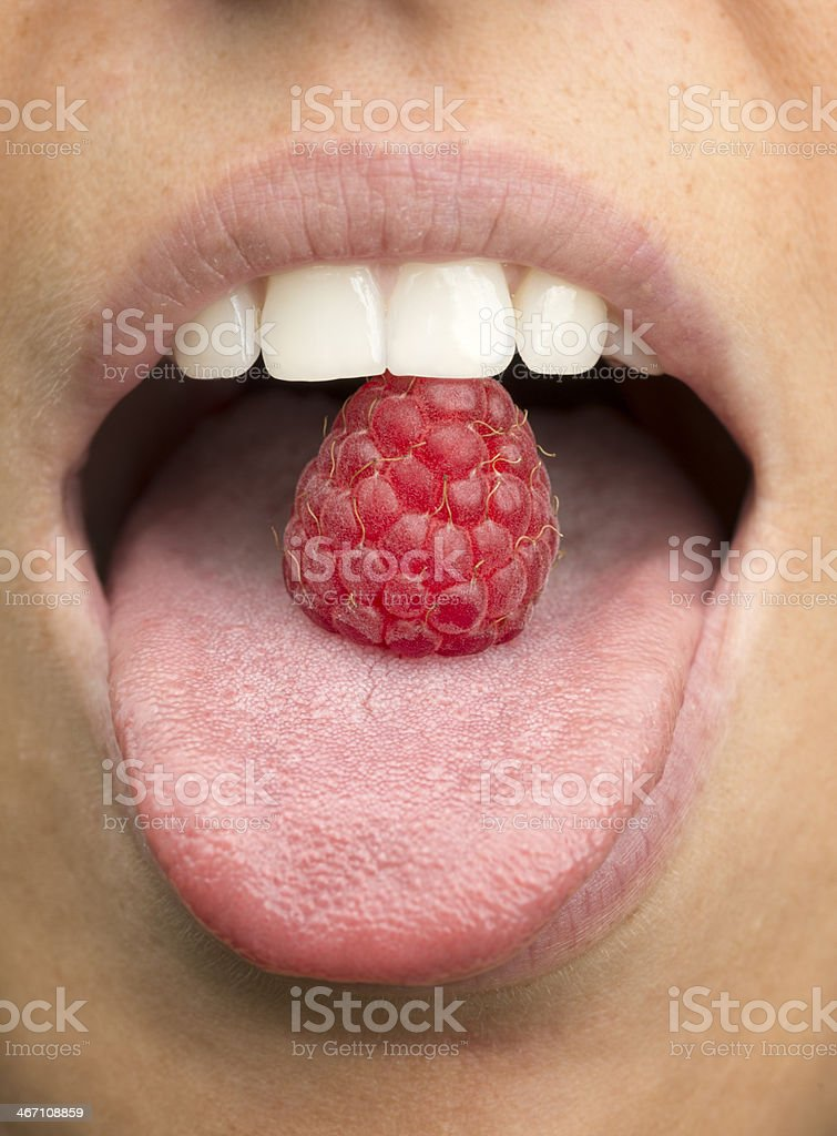 Mouth eating a Raspberry stock photo
