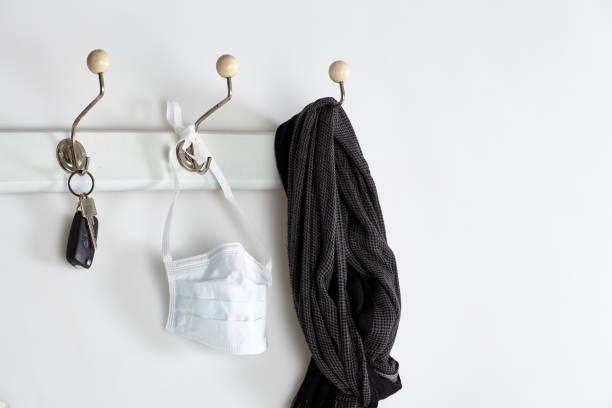 Mundschutz, Schal und Schlüssel hängen an der Garderobe – Foto