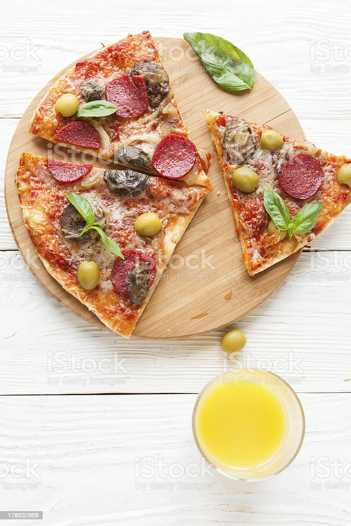 mouthwatering pizza with salami, cut into slices, top view royalty-free stock photo
