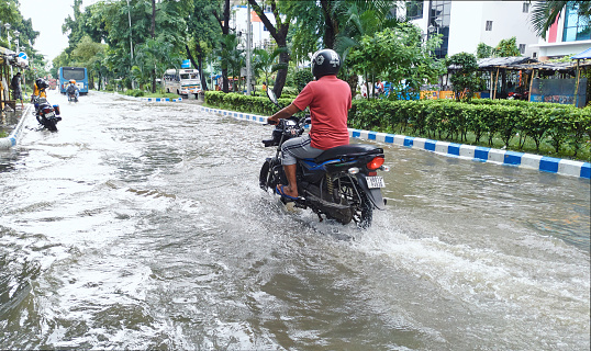 Kolkata, 07/30/2021: A person riding motorcycle through flooded streets of Saltlake Sector V, city's BPO and IT hub after a torrential monsoon rain disrupted citylife and flooded several parts of city.