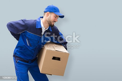 istock Mover Suffering From Backache While Carrying Parcel 1050851212