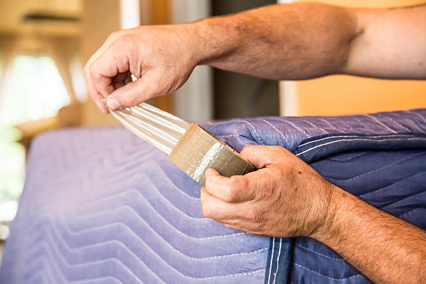 Mover taping protective blanket around furniture stock photo