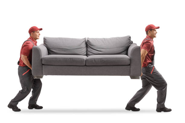 Movers carrying a couch Full length profile shot of two movers carrying a couch isolated on white background carrying stock pictures, royalty-free photos & images