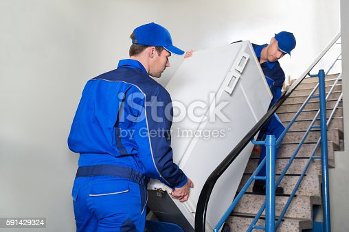 istock Movers Carrying Refrigerator On Steps 591429324
