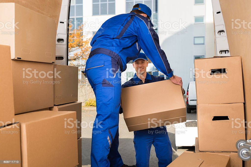 Movers Carrying Sofa Outside Truck On Street stock photo