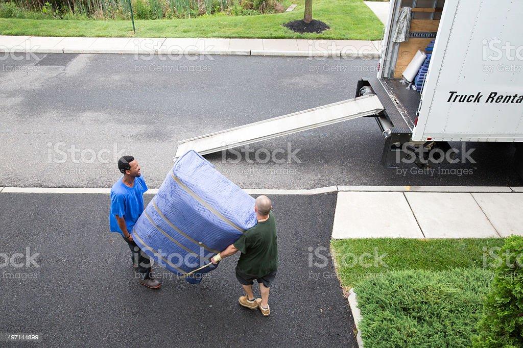 Movers get ready to load furniture onto moving van stock photo