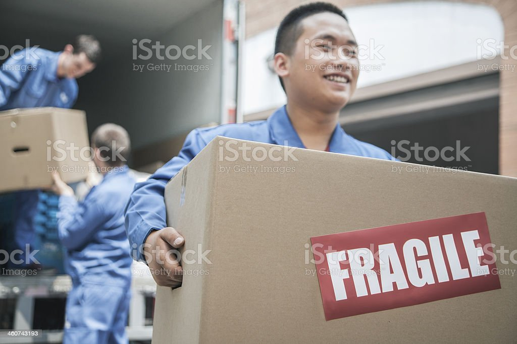 Movers unloading moving van and carrying a fragile box stock photo