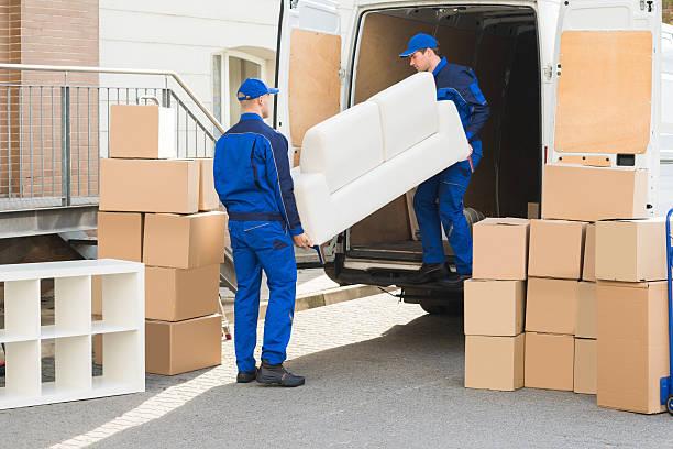 movers unloading sofa from truck - umzug transport stock-fotos und bilder