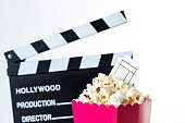 Movie clapper and pink popcorn bag with ticket in it with white background.