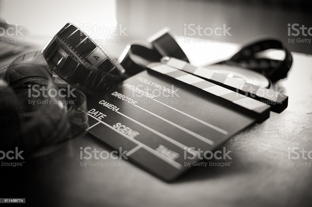 Movie clapper board and filmstrip selective focus stock photo