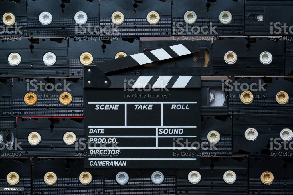 movie clapper on video cassette tapes stock photo