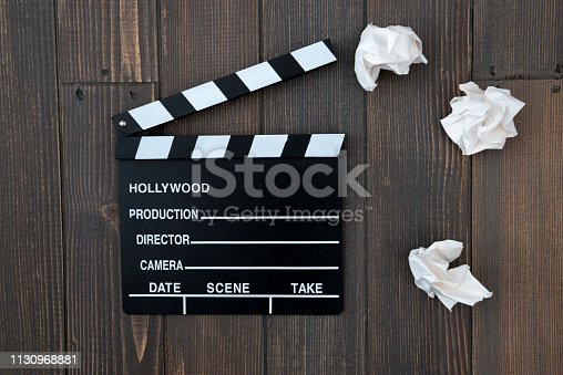 Movie clapper and white crumpled papers on wooden background.