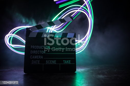 istock Movie concept. Miniature movie set on dark toned background with fog and empty space. Silhouette of vintage camera on tripod. 1224031372