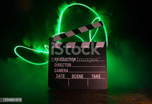 istock Movie concept. Miniature movie set on dark toned background with fog and empty space. Silhouette of vintage camera on tripod. 1224031373