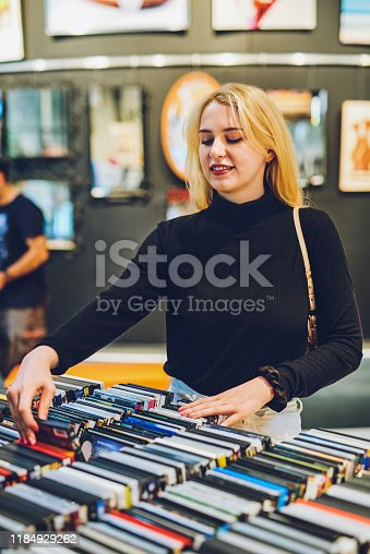 Shot of a young woman shopping for DVDs at a store