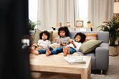 Full length shot of three adorable little boys eating popcorn and watching movies together at home
