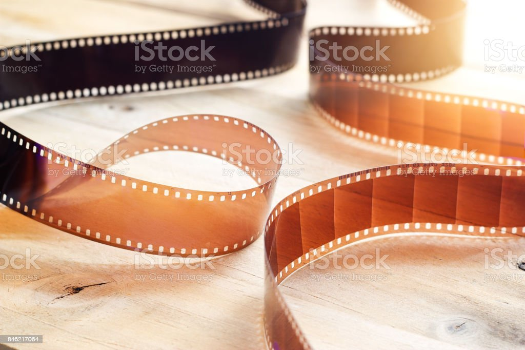 Movie film strips on wooden background stock photo
