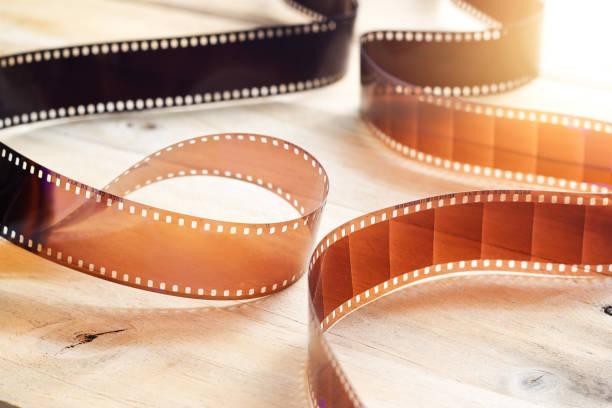 Movie film strips on wooden background stock photo