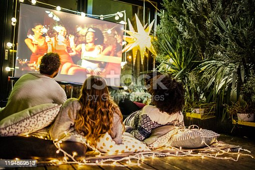 Friends making movie night at back yard