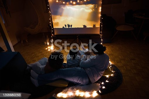 High angle view of relaxed African American family watching a movie in the living room.