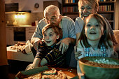 Close up of grandparents watching a movie together with their grandchildren