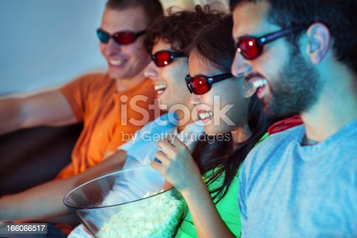 A group of friends watching a 3D movie and eating popcorn.
