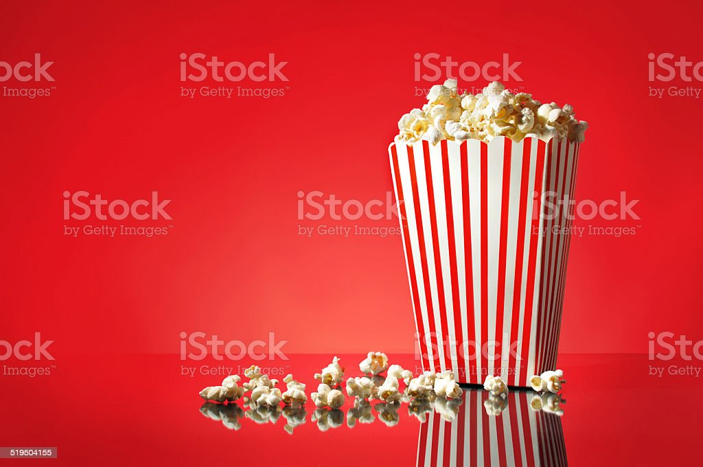 Movie Popcorn with 3D glasses Sitting on a Red Background stock photo