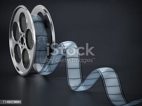 Movie reel and film strip standing on black reflective surface.