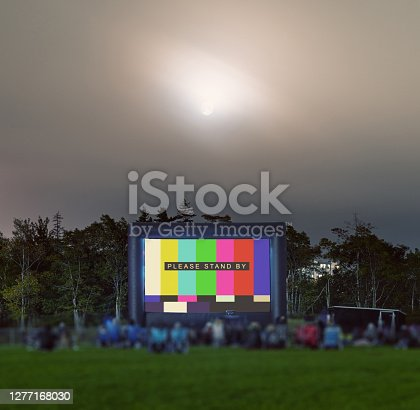 Movie goers enjoy a movie on a temporary pop up movie screen in a school soccer field with social distancing measures in place. Composite image with test pattern.